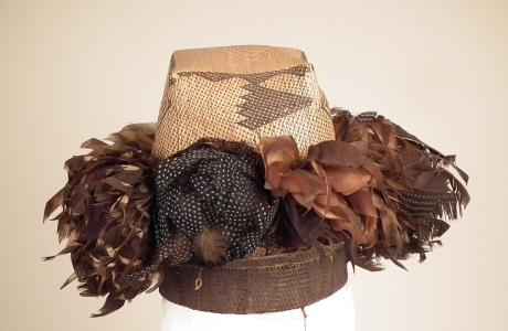 Plaited hat with bunches of feathers
